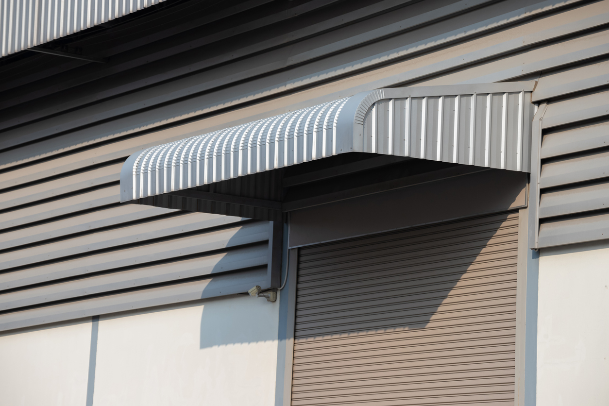 silver metal awning over shutter steel door of factory, steel awning.